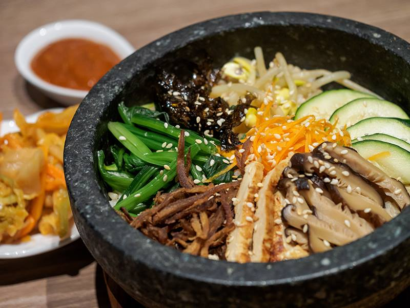 Bibimbap: A traditional Korean rice dish served in a hot pot that gives the rice a crispy finish at the end. It is served with our miso red bell pepper sauce and kimchi